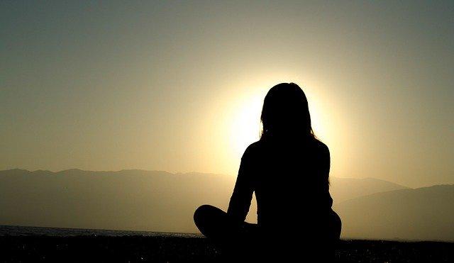 Ein Frau meditiert vor einem Sonnenuntergang