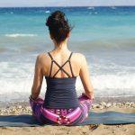 Eine Frau, die am Strand meditiert