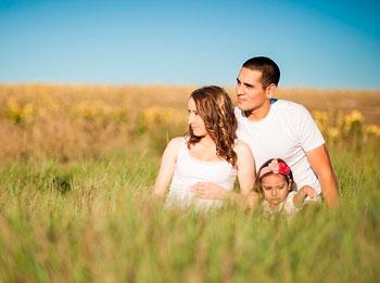 Paar sitzt mit Tochter in einem Feld